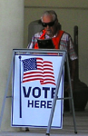 Pollworker sitting behind a sign that says Vote Here